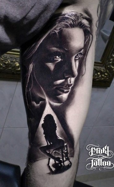 Black ink thigh tattoo of sexy woman with chair
