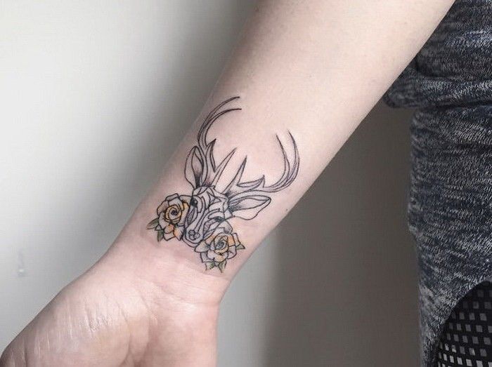 Black ink tiny wrist tattoo of deer with flowers