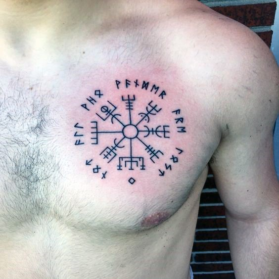 Black ink typical chest tattoo of ancient lettering