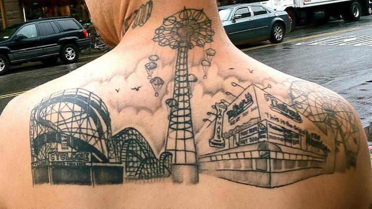 Black ink upper back tattoo of old roller coaster park