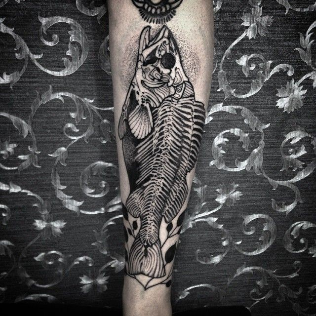Black ink very detailed forearm tattoo of fish skeleton