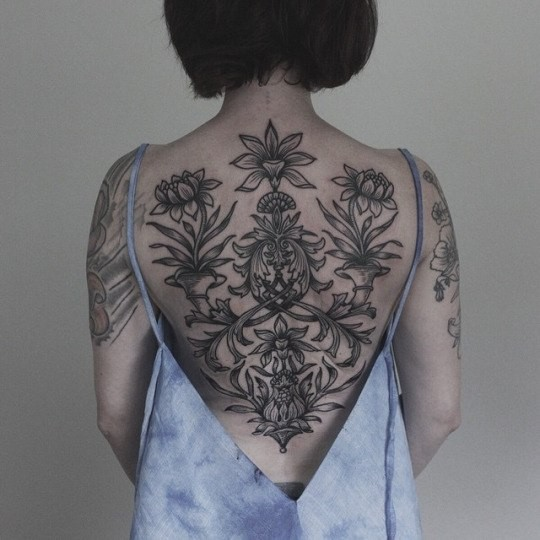 Black ink whole back tattoo of various flowers