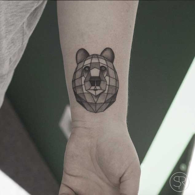 Black ink wrist tattoo of cartoon bear head