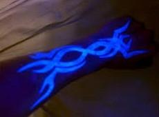 Black light fire tattoo on hand