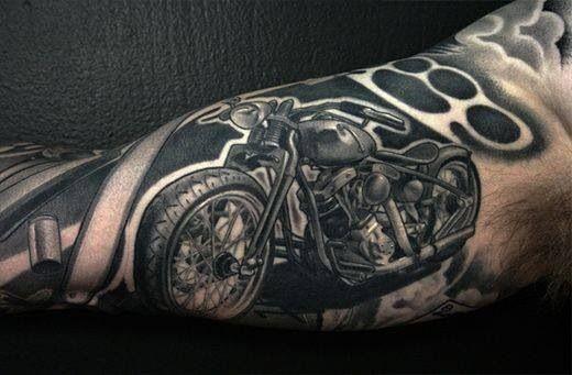 moto nero con tirapugni tatuaggio sul braccio