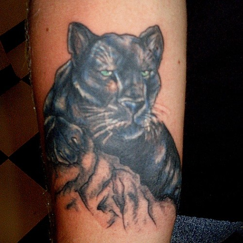 Black panther with green eyes tattoo on leg