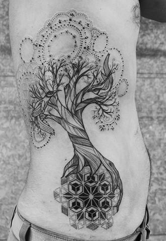 Black patchwork tree tattoo on ribs
