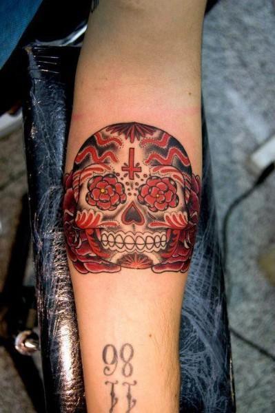 Black red sugar skull forearm tattoo
