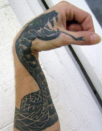 serpente nero con occhi verdi tatuaggio sul braccio