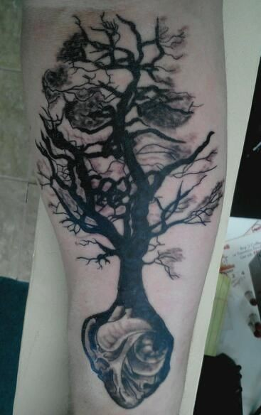 albero nero cresciuto dal cuore tatuaggio sul braccio