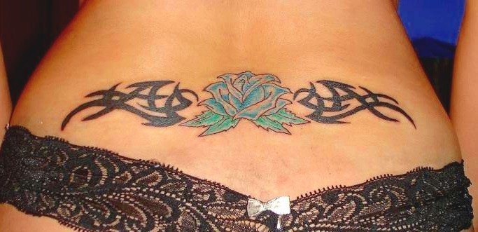 Black tribal with blue flower tattoo on lower back