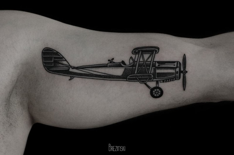 Black work style very detailed biceps tattoo of vintage plane