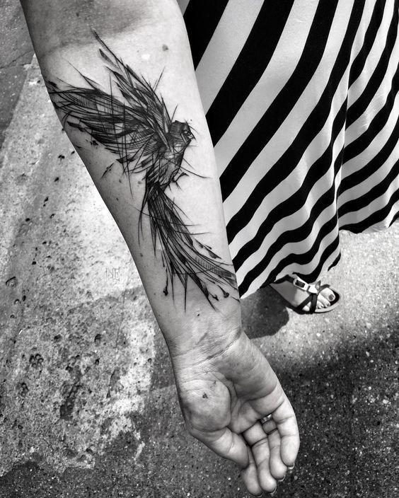 Tatuaggio di grande uccello in stile blackwork dipinto da Inez Janiak sull&quotavambraccio