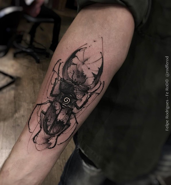 Blackwork style creative forearm tattoo of big black bug stylized with white vortex