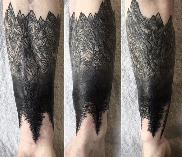 Blackwork style forearm tattoo of mountains with trees