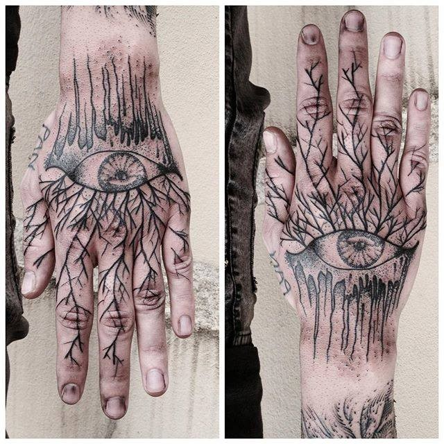 Blackwork style hand tattoo of human eye with tree branches