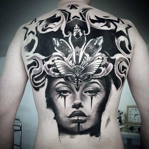 Blackwork style impressive looking back tattoo of woman face with big butterfly and stars