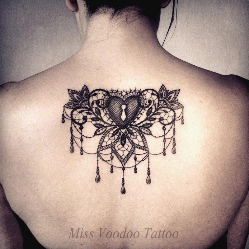 Blackwork style impressive looking upper back tattoo of heart shaped lock with flowers by Caro Voodoo
