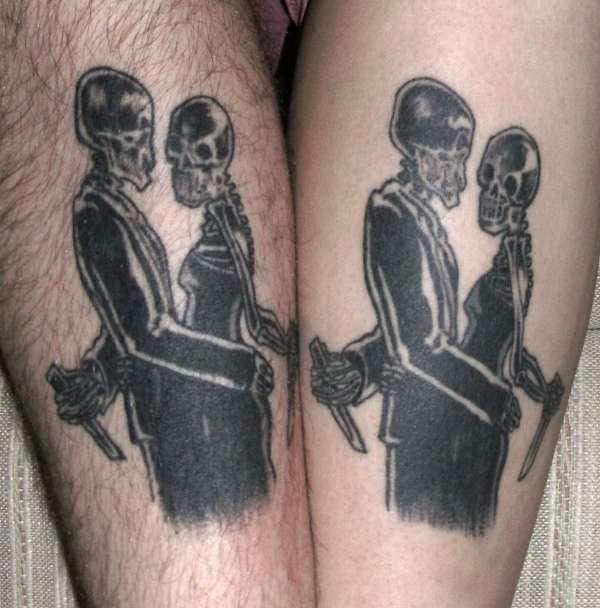 Blackwork style leg tattoo of skeleton couple