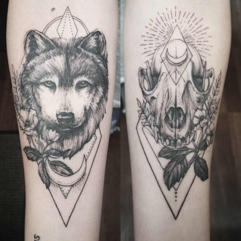 Blackwork style nice looking forearm tattoo of wolf skulls with flowers