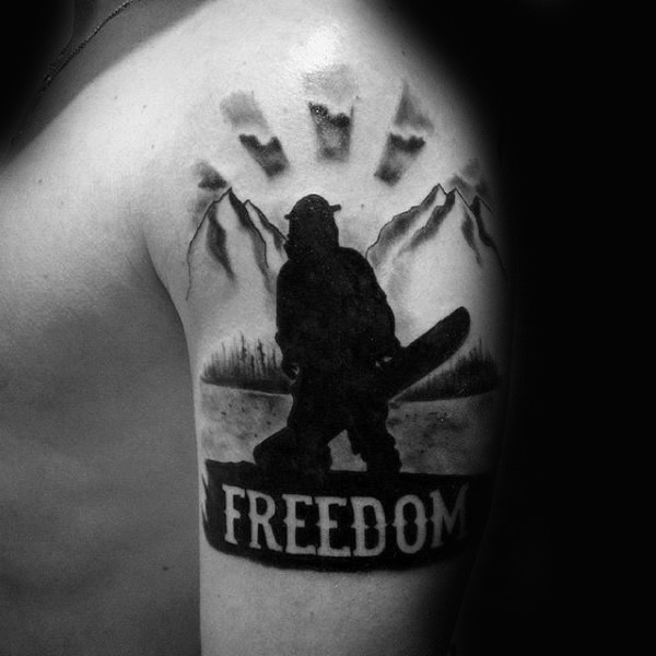 Blackwork style of medium size shoulder tattoo of man with snowboard and lettering