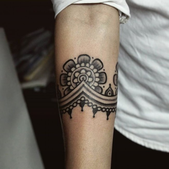 Blackwork style simple looking forearm tattoo of nice floral ornament