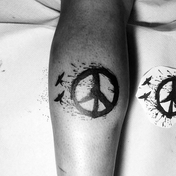 Blackwork style small black ink pacific symbol with birds tattoo on leg