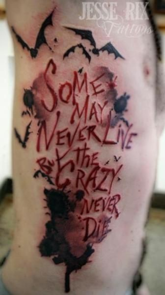 Bloody colored sharp lettering side tattoo with paint drips and bats by Jesse Rex