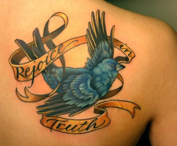Tatuaggio colorato sulla spalla l&quotuccello & la striscia con la scritta