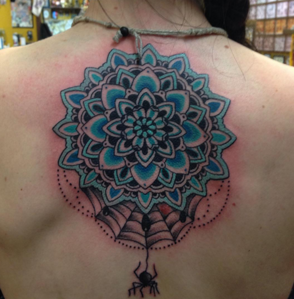 Blue colored illustrative style back tattoo of cool flower with small spider