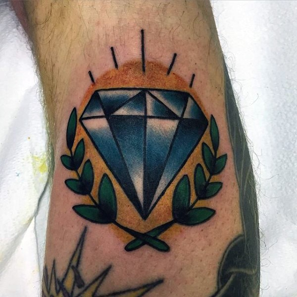 Blue colored little diamond with sun tattoo on arm