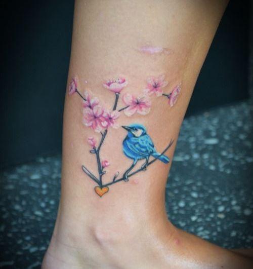 carino colorato uccello blu su ramo di albero fiorito tatuaggio su caviglia