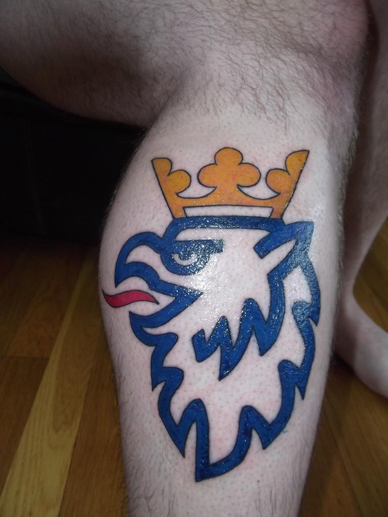 Tatuaje en la pierna, símbolo de grifo azul con corona