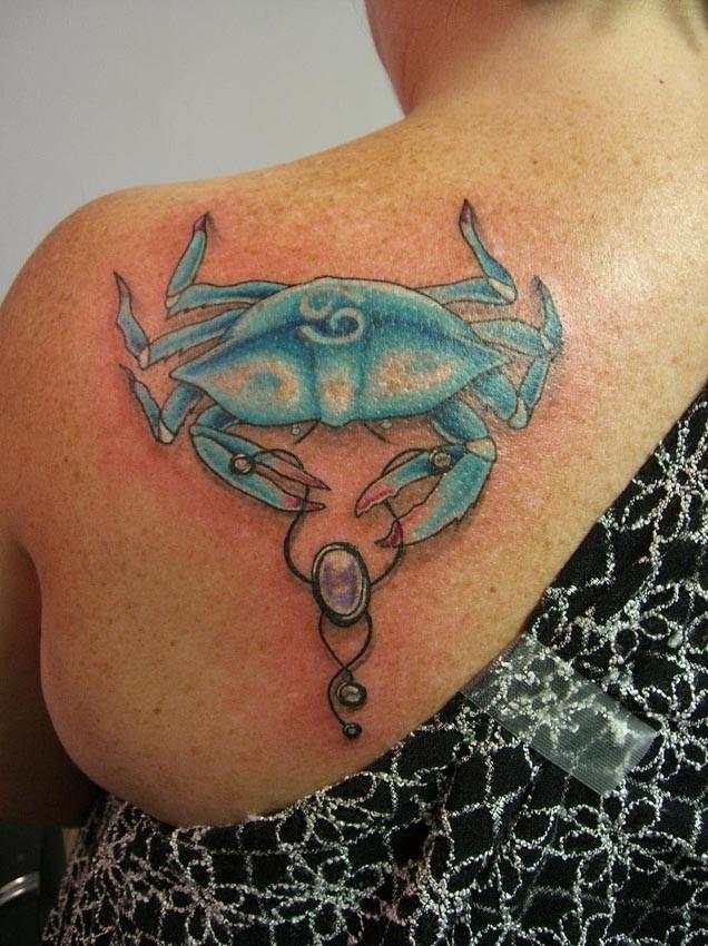 Tatuaje en la espalda, cangrejo azul claro con joya