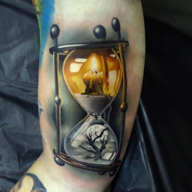Breathtaking 3D realistic multicolored sand clock tattoo on arm stylized with old tree and candle