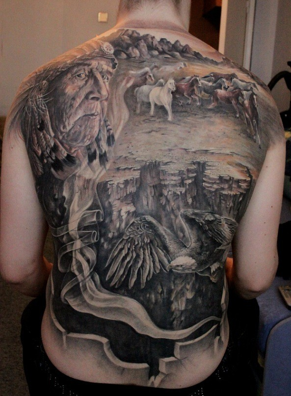Breathtaking American native colored whole back tattoo of old Indian with running horses in desert and flying eagle