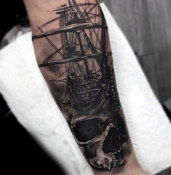 Breathtaking realism style colored forearm tattoo of sailing ship with human skull
