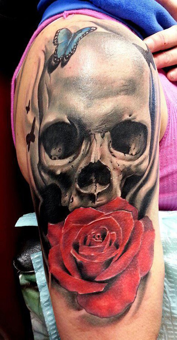 Breathtaking realism style colored large shoulder tattoo of small butterfly with skull and rose flower