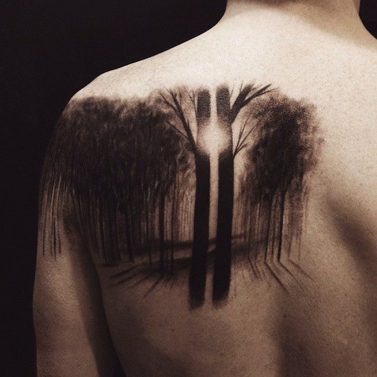 Breathtaking stippling style black ink scapular tattoo of dark forest with sun