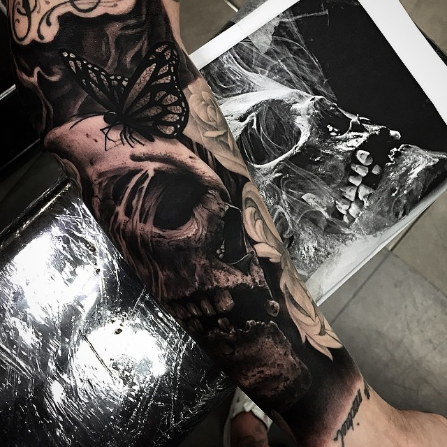 Breathtaking very detailed human skull tattoo on forearm combined with flowers and butterfly
