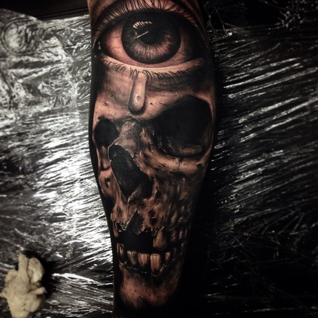 Breathtaking very detailed human skull tattoo on forearm combined with mystic eye