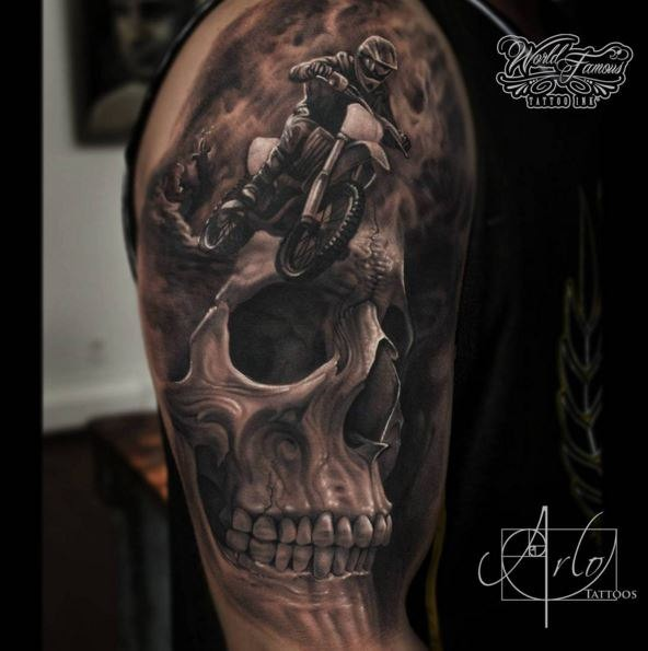 Breathtaking very detailed shoulder tattoo of human skull with bike rider