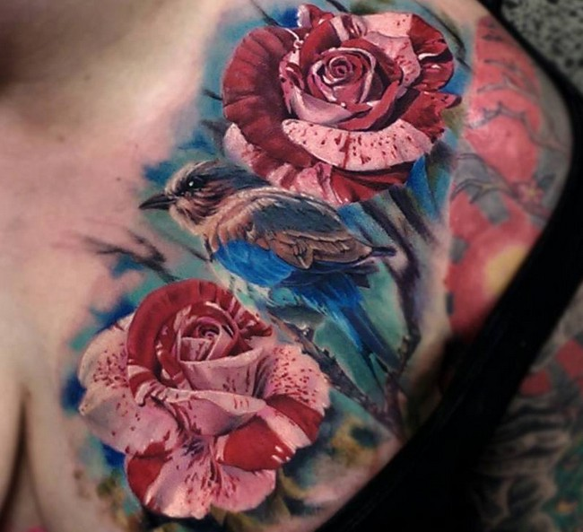 Breathtaking very realistic painted and colored flowers with little bird tattoo on chest