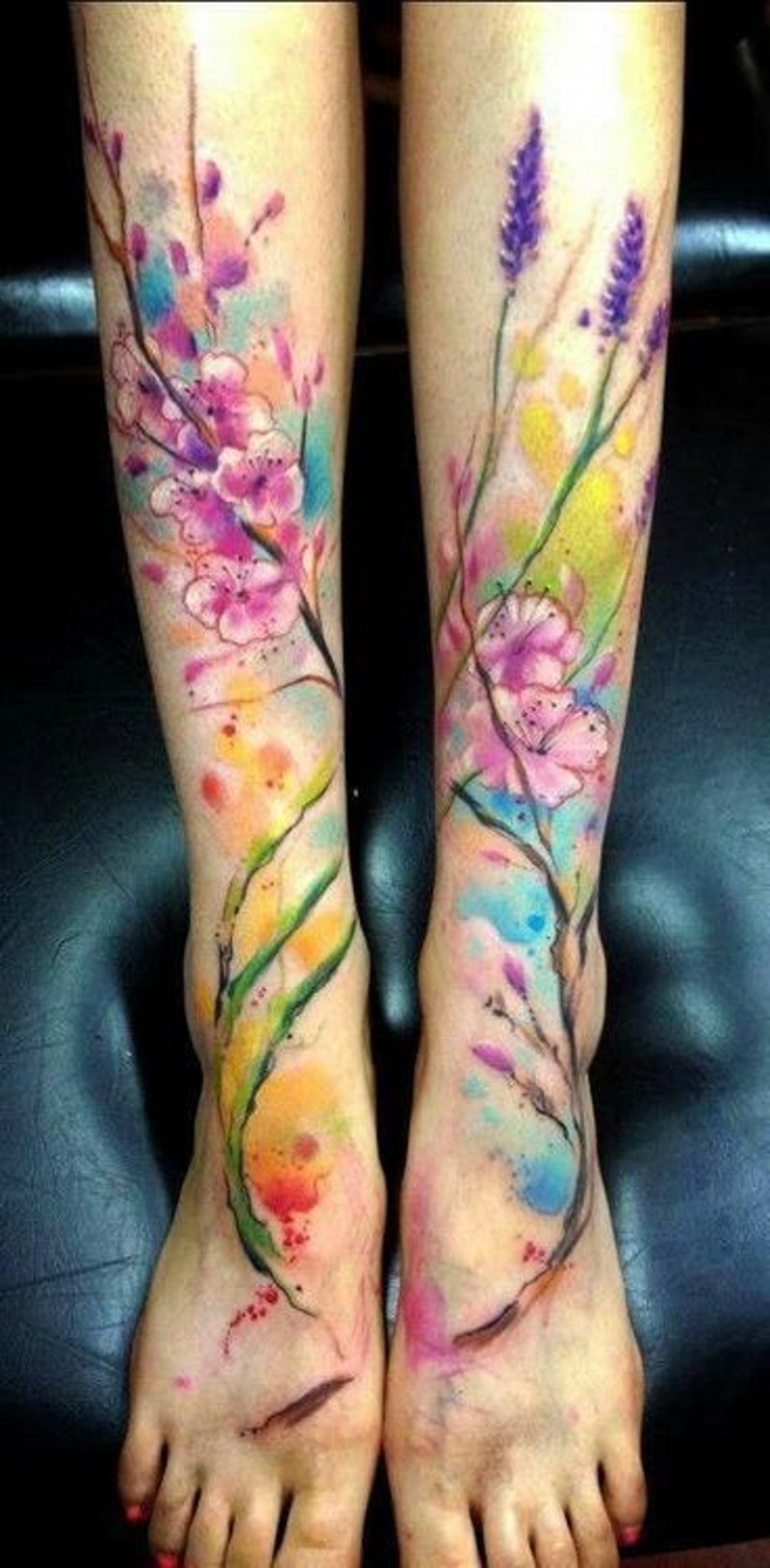 Bright colored flowers and pink blossoms on branch watercolor tattoo on both legs