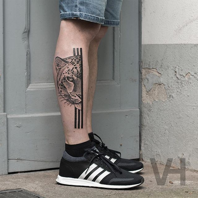 Brilliant designed by Valentin Hirsch black ink leg tattoo of split leopard head with black lines
