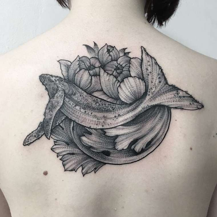 Brilliant natural looking whale with flowers tattoo on back area