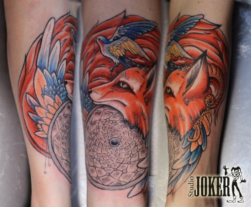 Brilliant painted dream catcher shaped colored fox with bird tattoo on arm