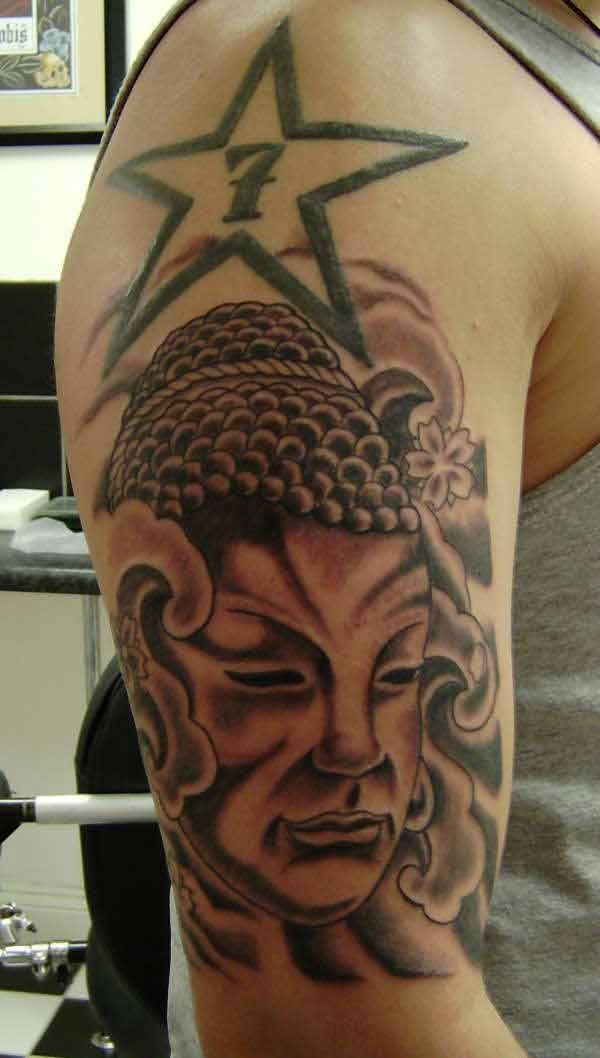 Buddhist face with buddhist symbols tattoo on arm