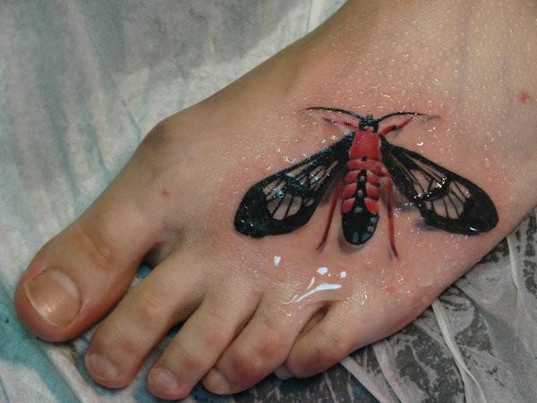 Tatuaggio colorato 3D sul piede la farfalla nera rossa