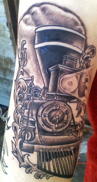 Carelessly painted black ink upper arm tattoo of big train